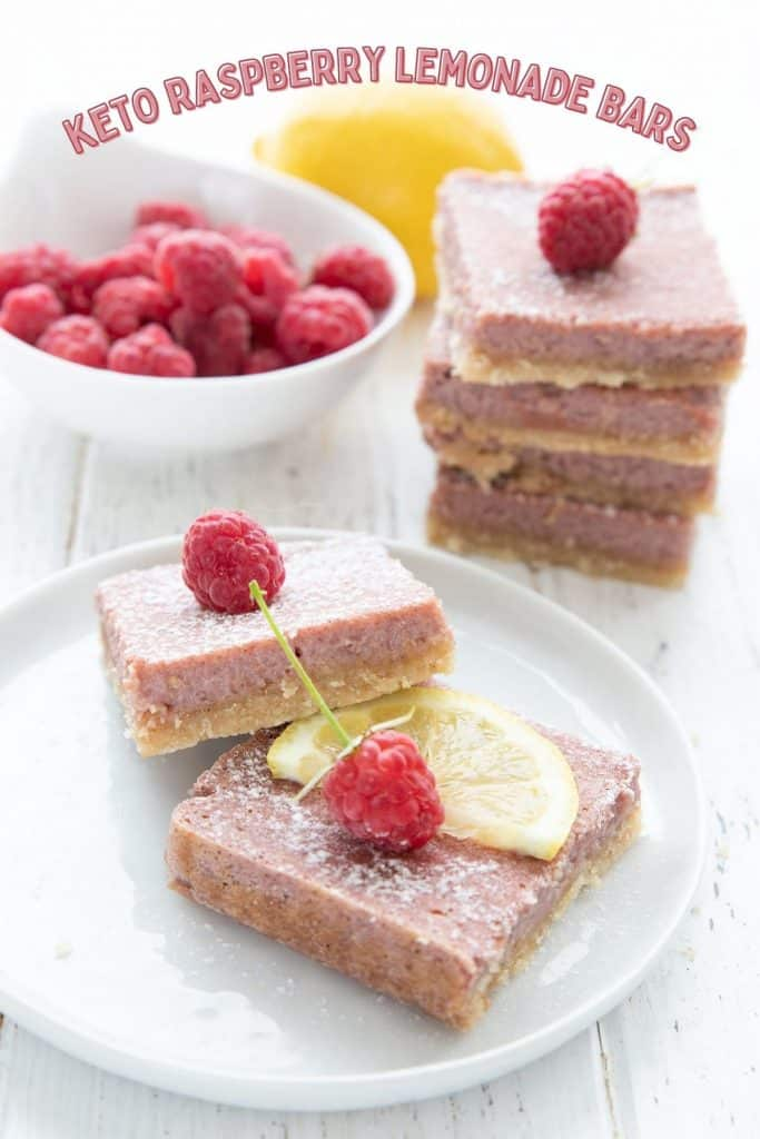 Titled image of keto raspberry lemonade bars on a white plate with a bowl of raspberries and a lemon in the background.