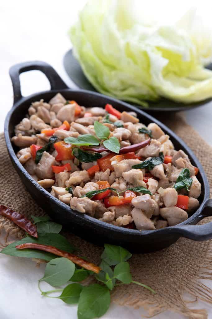 Thai basil chicken in a cast iron serving dish, in front of a bowl of lettuce cups.