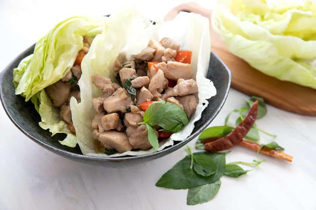 Thai basil chicken in lettuce wraps in a black bowl.