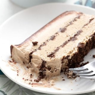 A slice of keto coffee ice cream cake on a white plate over a blue patterned napkin.