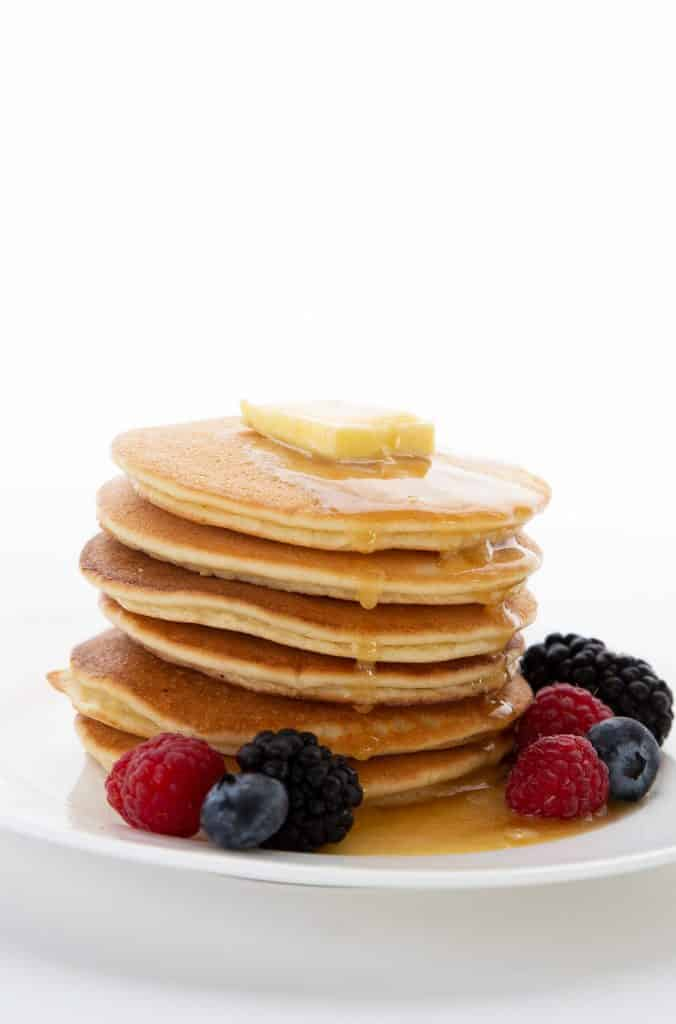 A stack of almond flour keto pancakes on a white plate on a white background.