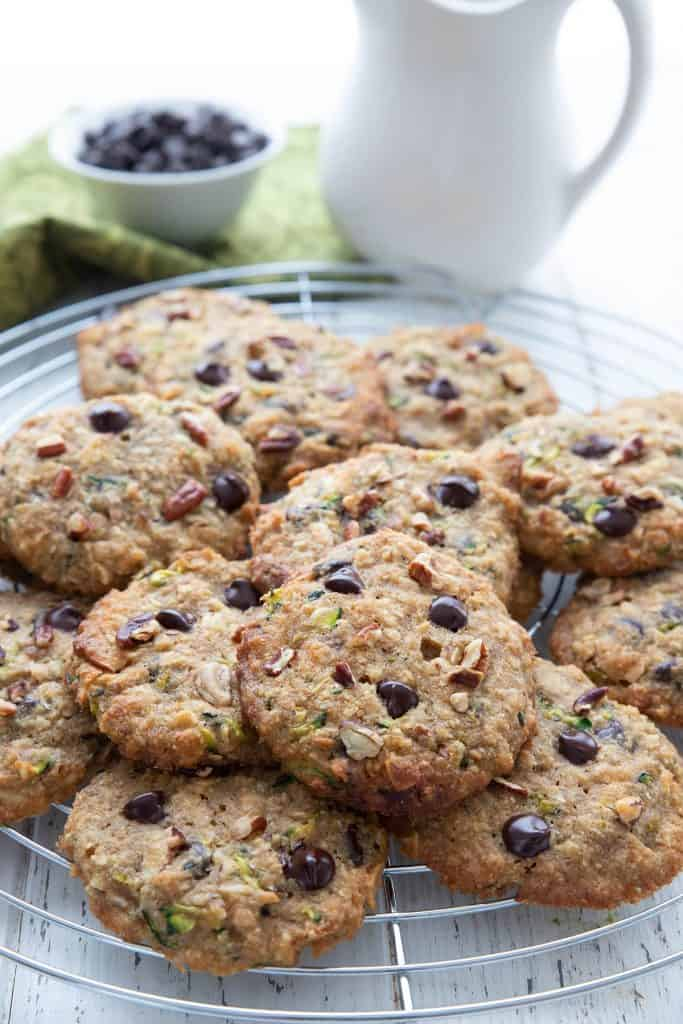 A cooling rack piled up with keto zucchini chocolate chip cookies.