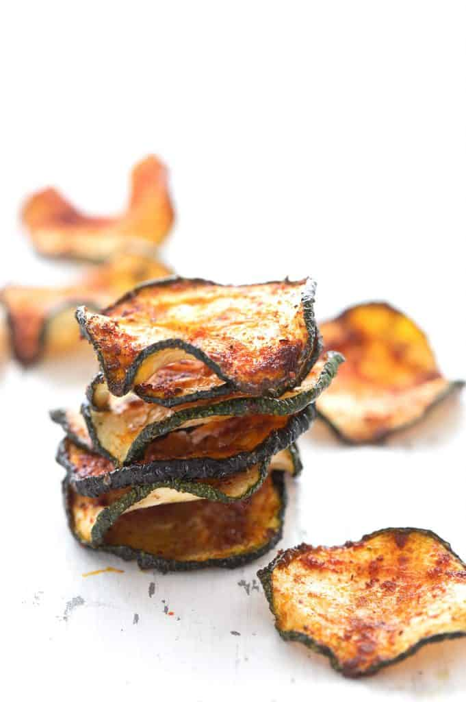 A stack of baked zucchini chips on a white table.
