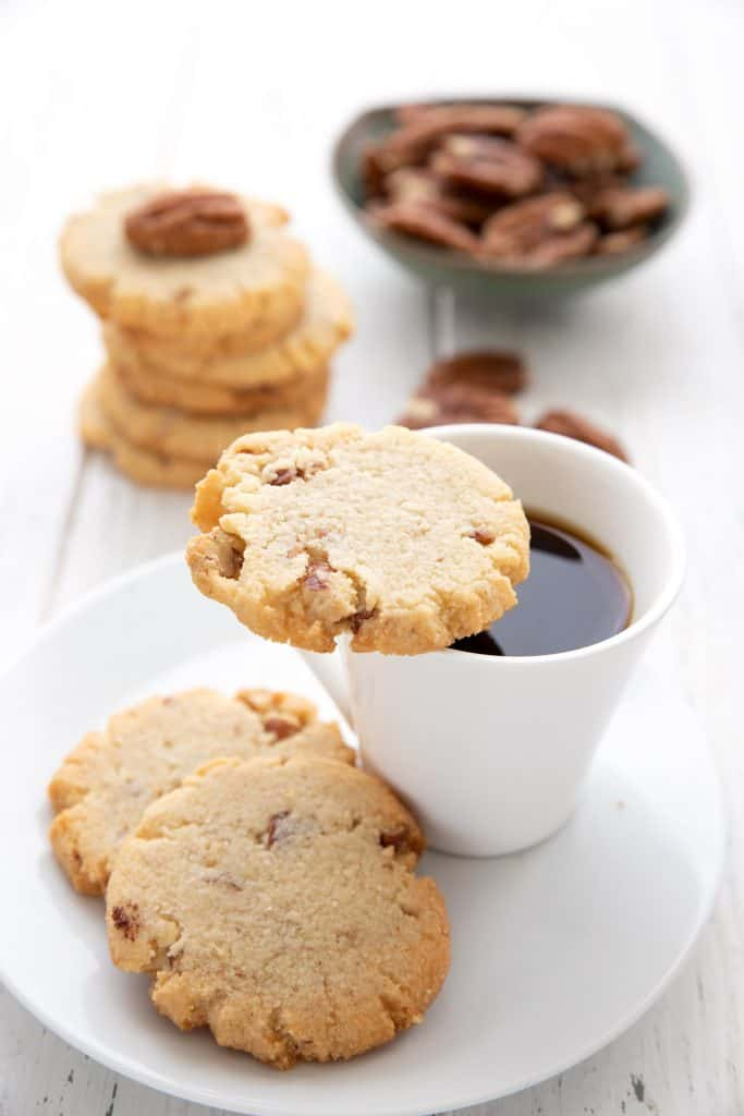 A crispy butter pecan cookie sits on the edge of a cup of coffee, with two more cookies on the plate and a bowl of pecans in the background.