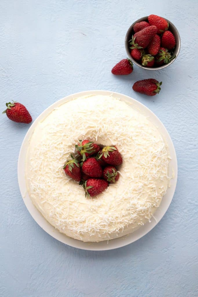 Top down image of keto coconut bundt cake with strawberries in the center.