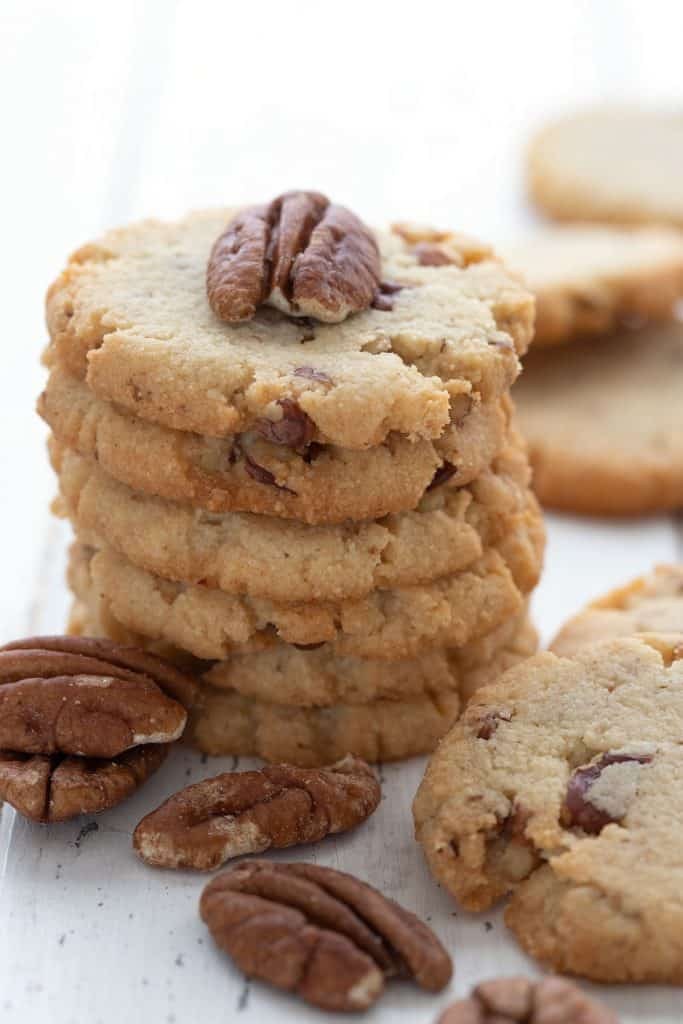 Close up shot of a stack of low carb butter pecan cookies with pecans scattered around.