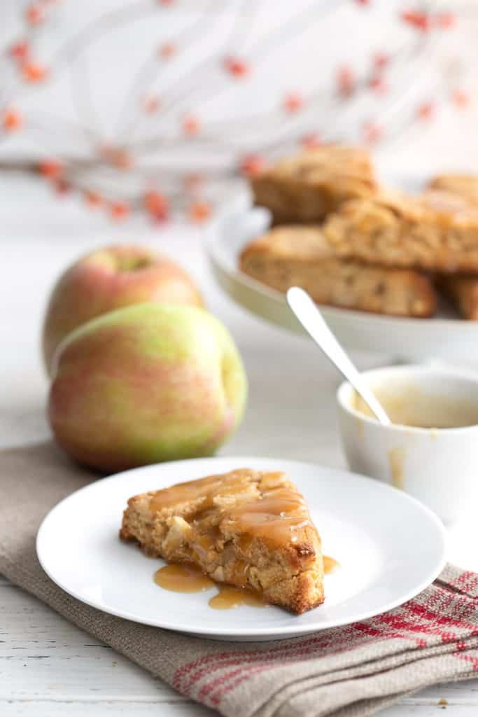 A keto caramel apple scone on a white plate in front of some apples and a bowl of caramel sauce.