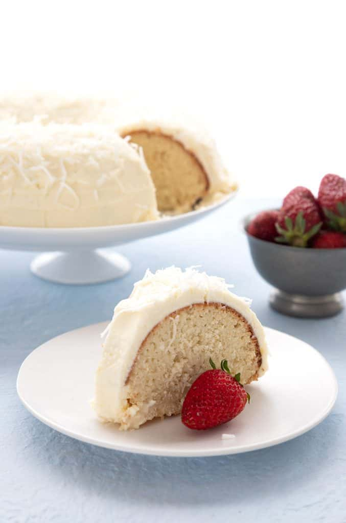 A slice of keto coconut cake on a white plate with a bowl of strawberries and the rest of the cake in the background.