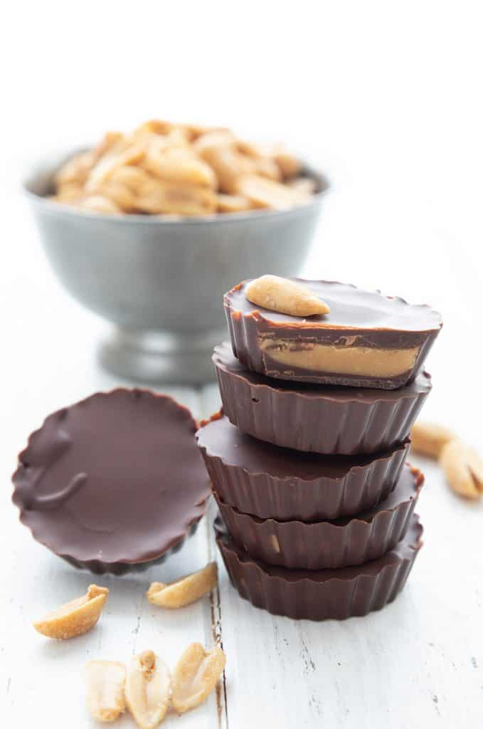 A stack of peanut butter cups sits in front of a bowl of peanuts.