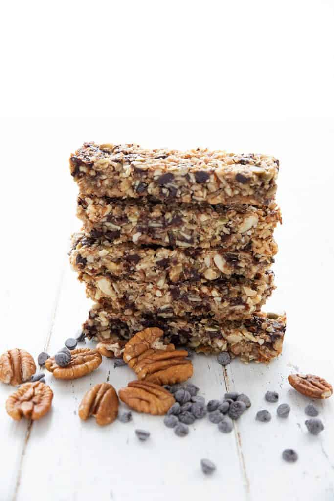 A stack of keto granola bars on a white wooden table, with pecans and chocolate chips scattered around.