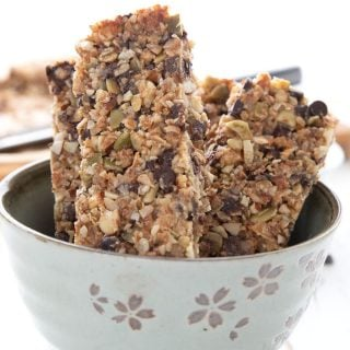 Titled image of keto granola bars standing up in a light green bowl.