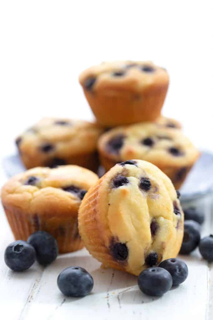 A stack of keto blueberry muffins on a white table with blueberries around it.
