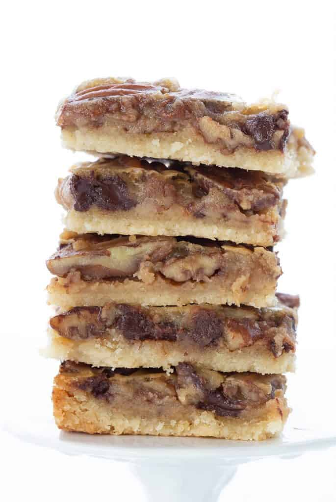 A stack of keto pecan pie bars on a cupcake stand.