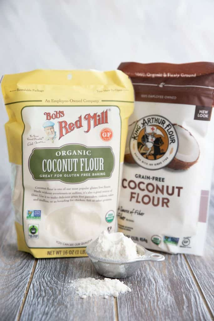 Two bags of coconut flour sit on a wooden table with a measuring cup full of the flour in front.
