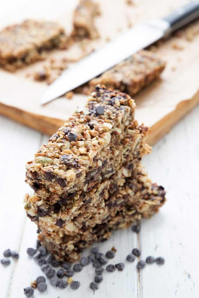 A stack of keto granola bars in front of a cutting board with the remaining bars on it.