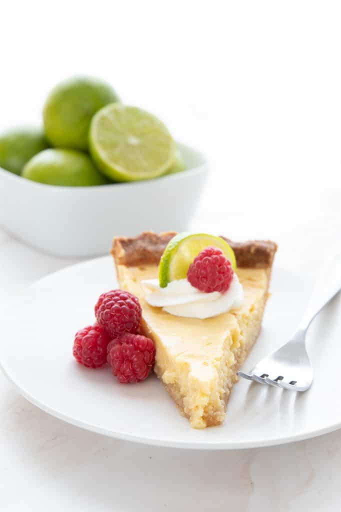 A slice of keto key lime pie on a white plate in front of a bowl of key limes.