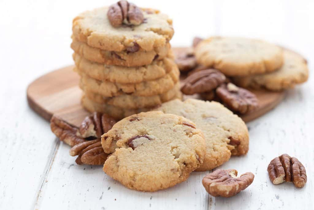 Keto butter pecan cookies and pecans scatted around on a wooden cutting board.