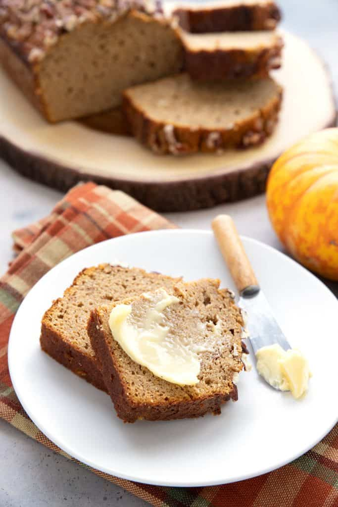 A slice of keto pumpkin bread with butter on it, on a white plate over a plaid napkin.