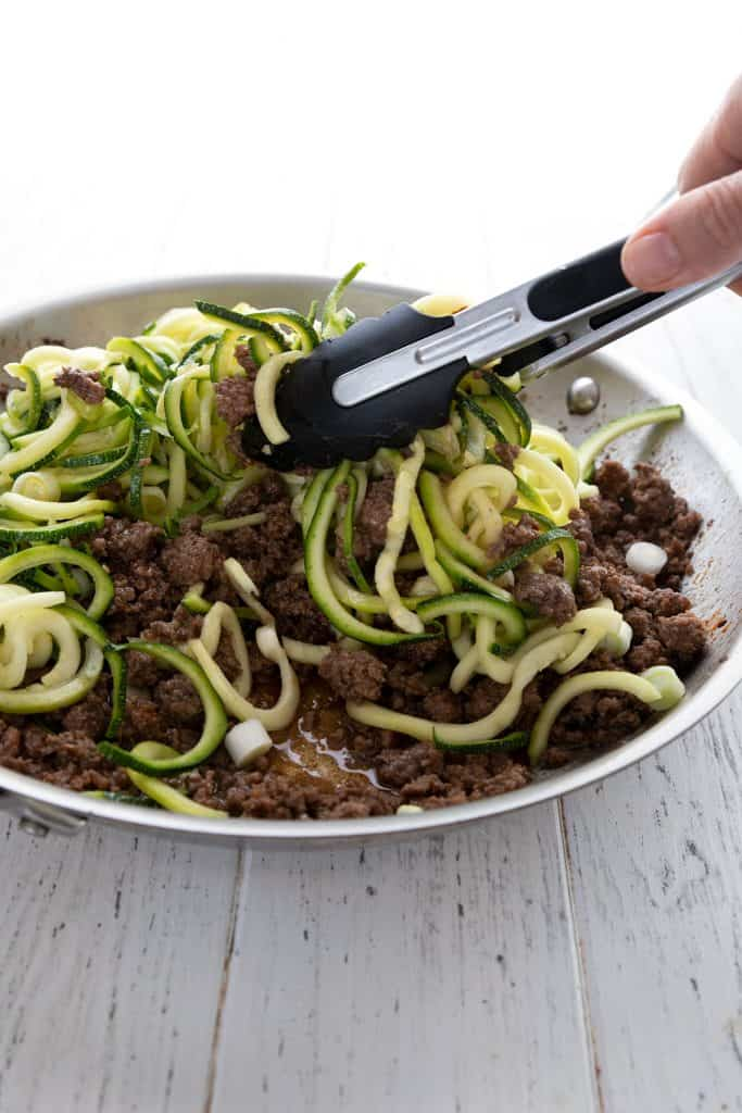 Tossing beef and zucchini noodles together in a pan for keto Korean Beef
