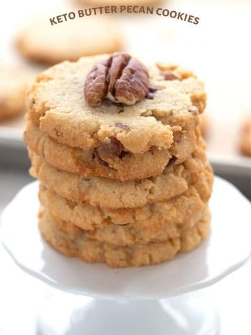 Titled image of a stack of keto butter pecan cookies on a cupcake stand.