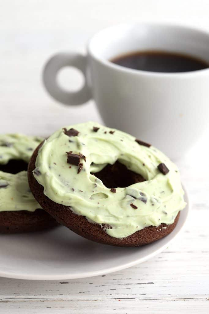 Two mint chip donuts sit on a white plate with a cup of coffee in the background.