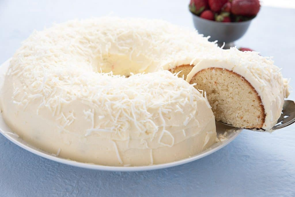 A sugar free keto coconut cake on a white plate with a slice being lifted out of it.