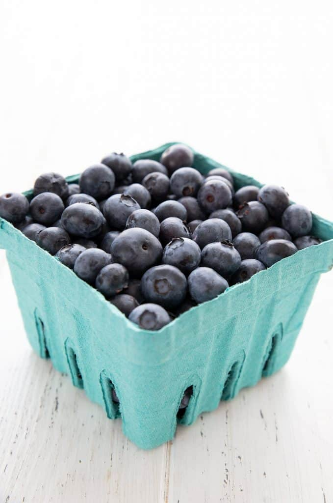 Oregon blueberries in a pint basket on a white table.