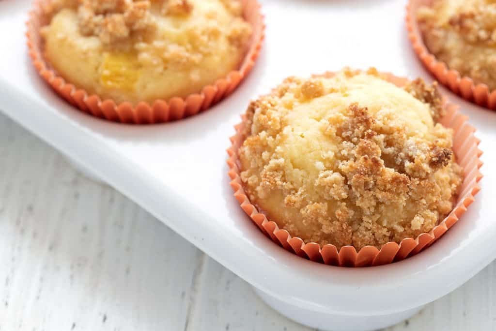 Close up shot of a peach muffin in an orange paper liner, in the muffin pan.