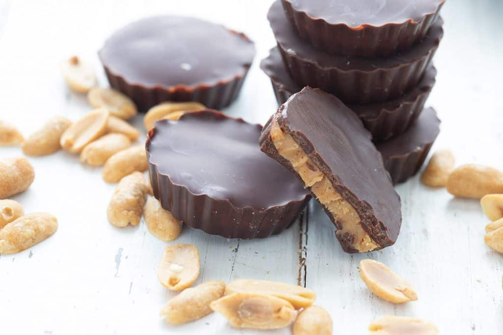 Keto peanut butter cups on a white table with peanuts scattered around.