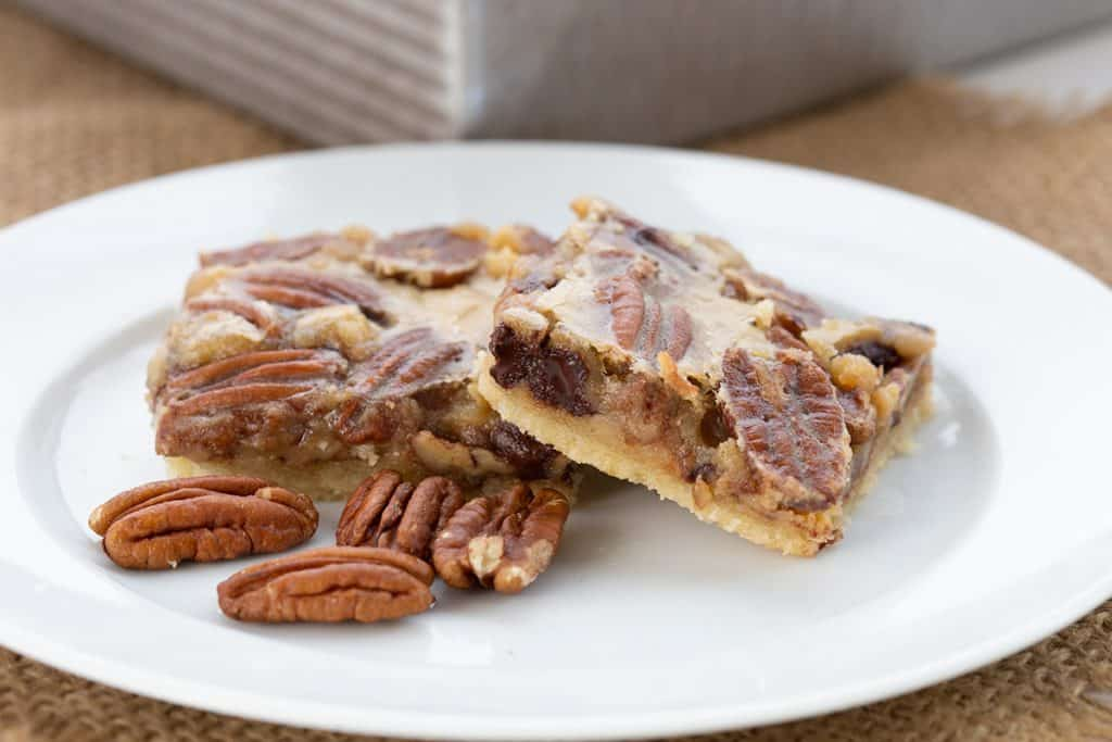 Two keto chocolate pecan pie bars on a white plate.