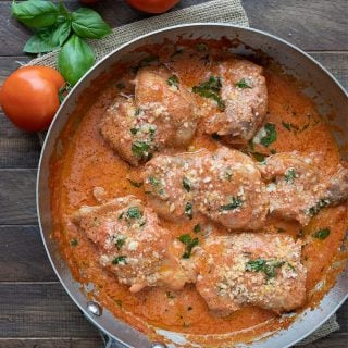 Top down image of keto tomato basil chicken in the pan on a wooden table.