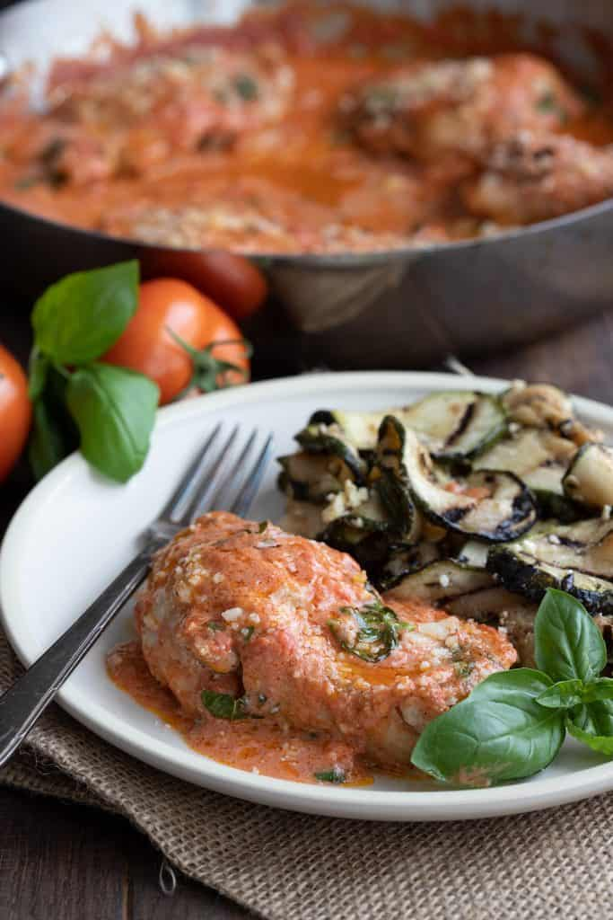 Creamy Tomato Basil Chicken on a plate with grilled zucchini.
