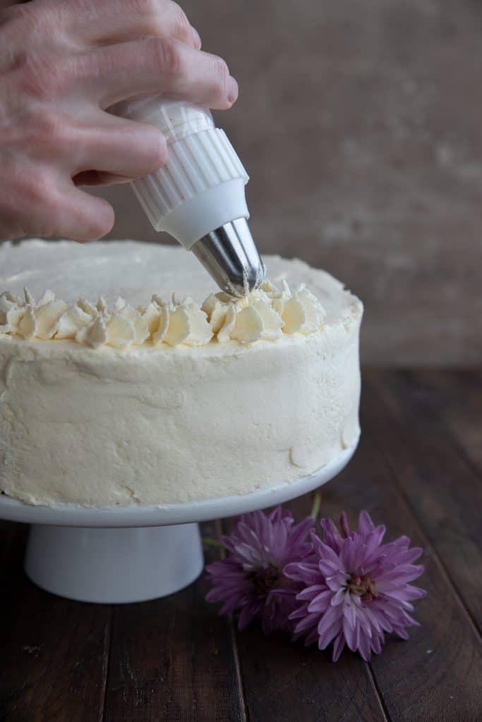Piping vanilla frosting on a keto vanilla cake.