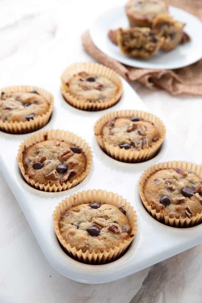 Keto pecan pie muffins in a white ceramic muffin pan.
