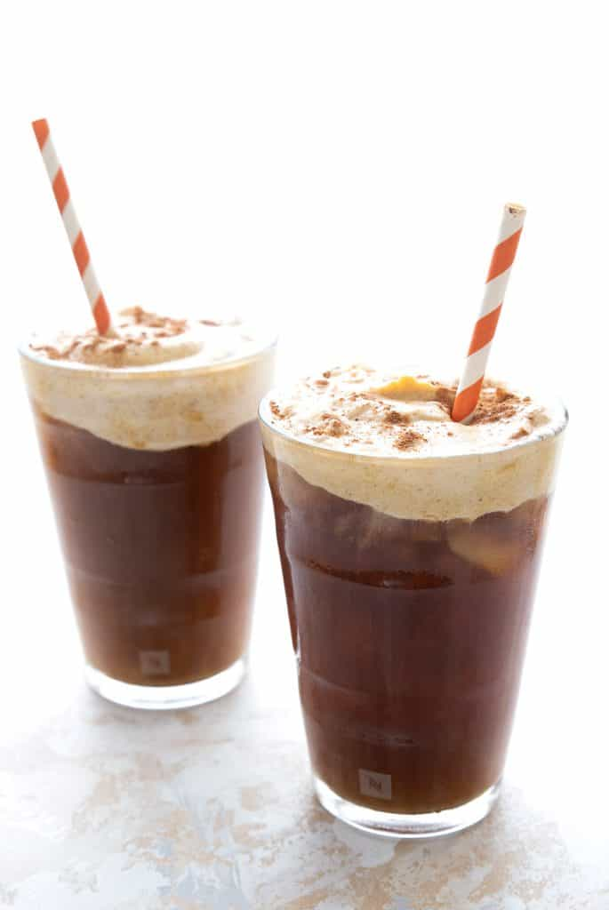 Two glasses of cold brew coffee with sugar free pumpkin cream on top.