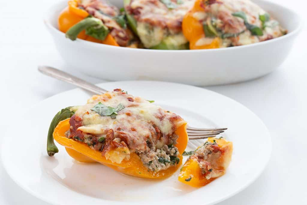 A close up shot of keto stuffed peppers on a white plate with a fork.