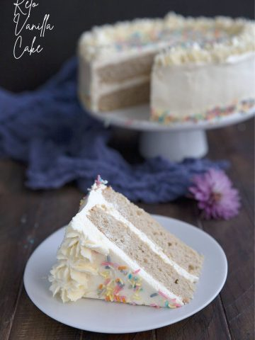 Titled image of a slice of keto vanilla cake on a white plate, in front of a cake plate with the rest of the cake.