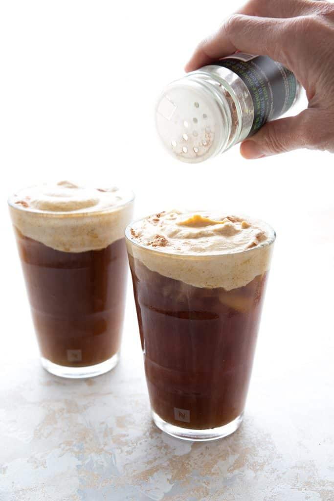 Sprinkling pumpkin spice on keto cold brew coffee.