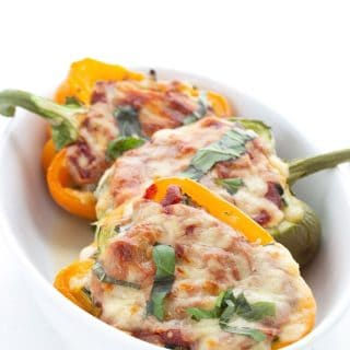 Titled image of keto lasagna stuffed peppers in a white ceramic baking dish.