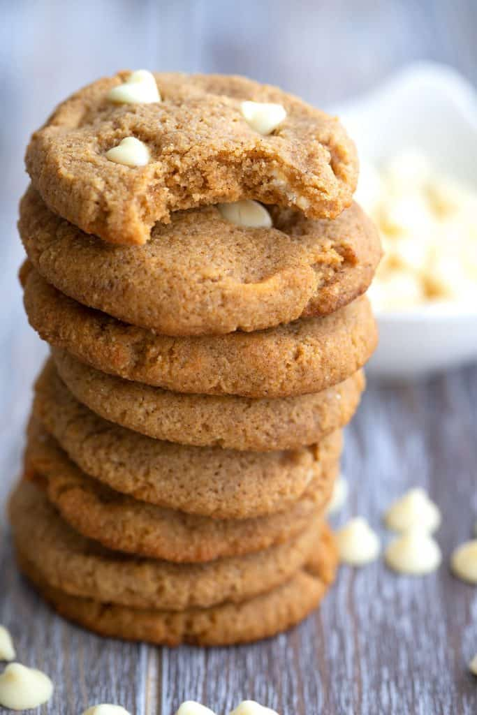 A stack of keto pumpkin cookies with white chocolate chips on a wooden table with a bite taken out of the top one.