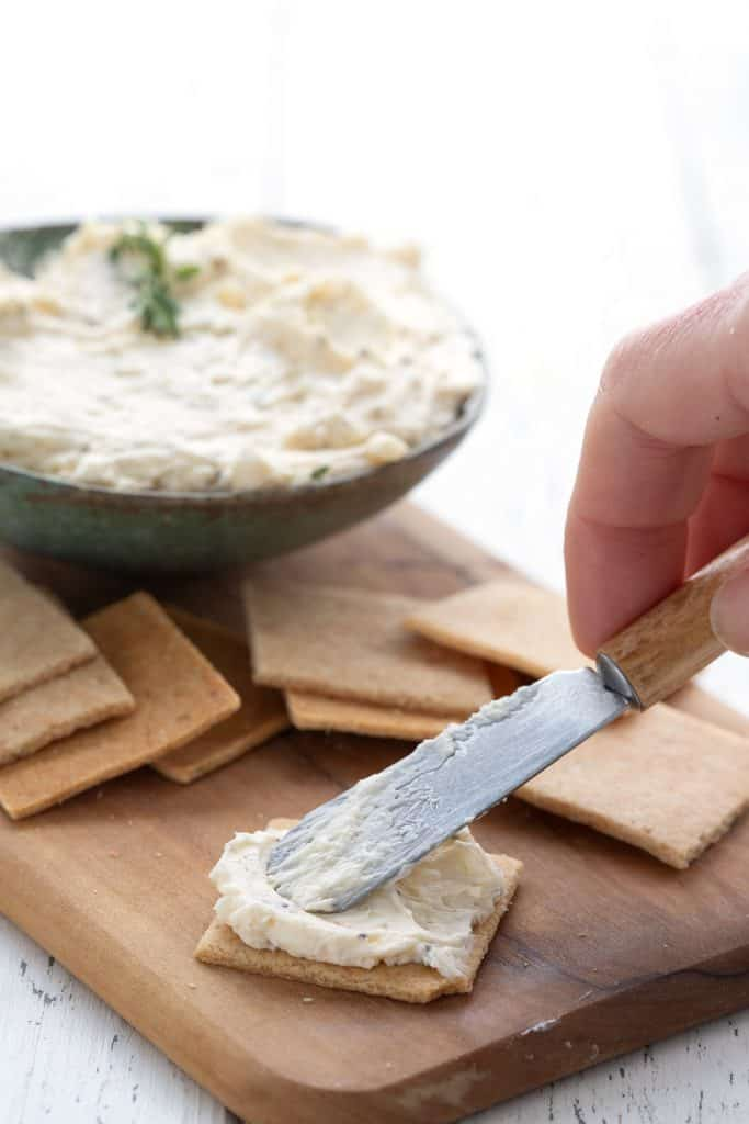 A small cheese knife spreading homemade Boursin on a keto cracker.