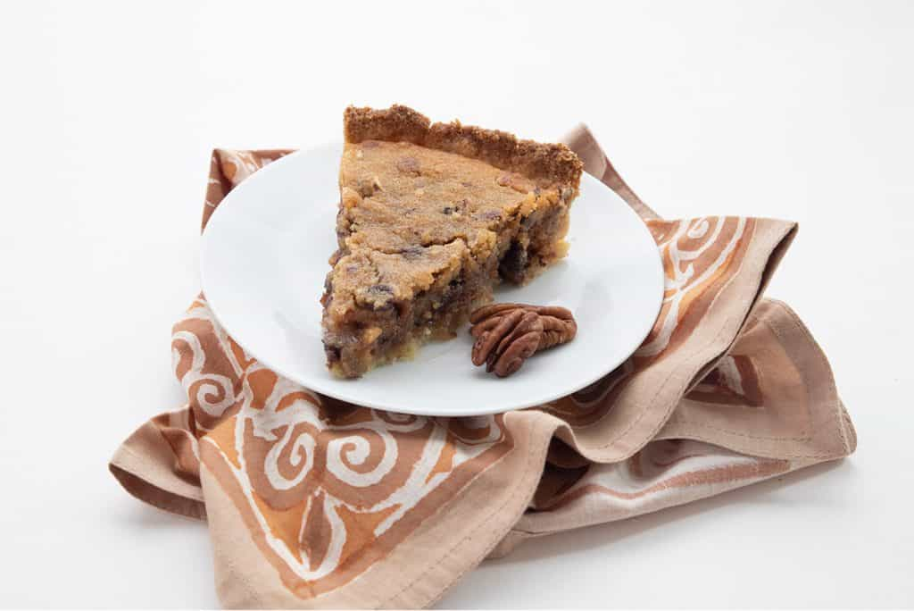 A slice of Keto Kentucky Chocolate Chip Cookie Pie with pecans on the side, over a pattered brown napkin.