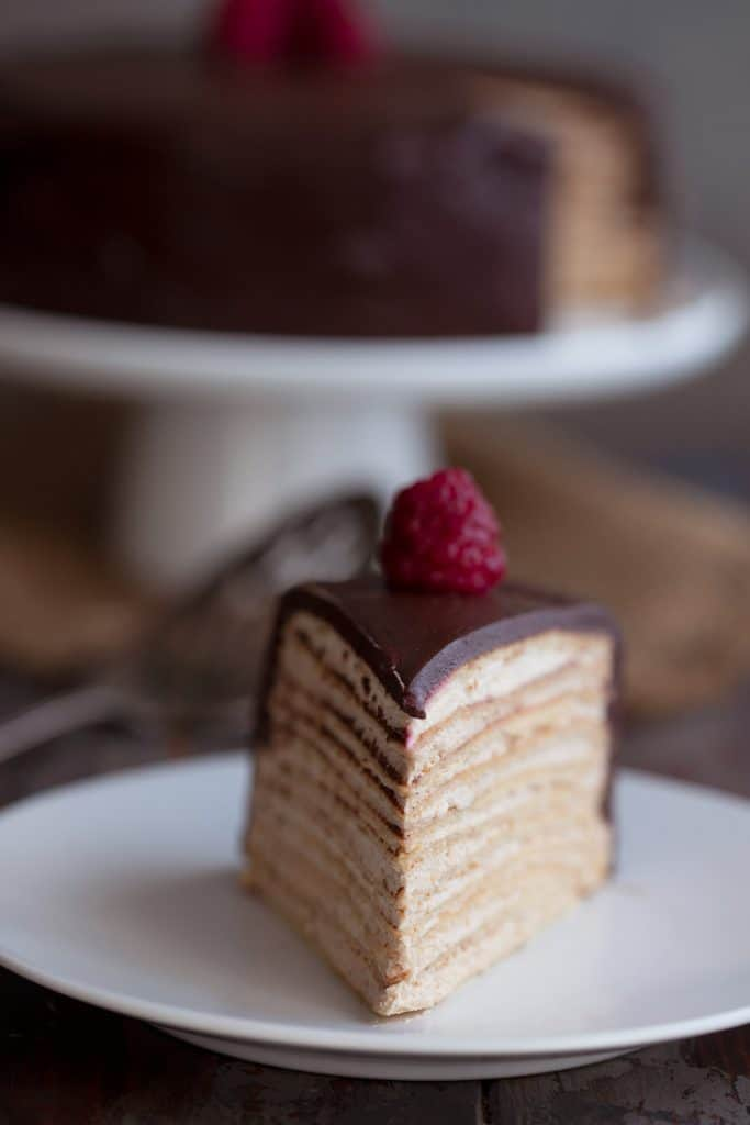 A slice of keto crepe cake on a white plate with a raspberry on top.