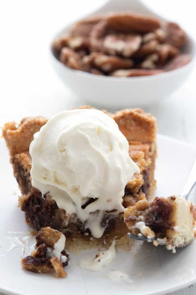 Close up shot of Keto Kentucky Derby Pie with ice cream on top, with several bites taken out of the pie.