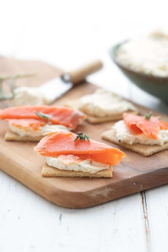 Keto crackers on a wooden cutting board topped with homemade Boursin cheese and smoked salmon.