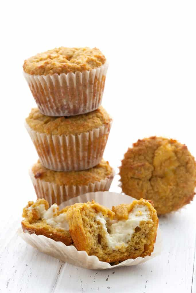 A stack of keto pumpkin cream cheese muffins with one broken open to show the creamy inside.