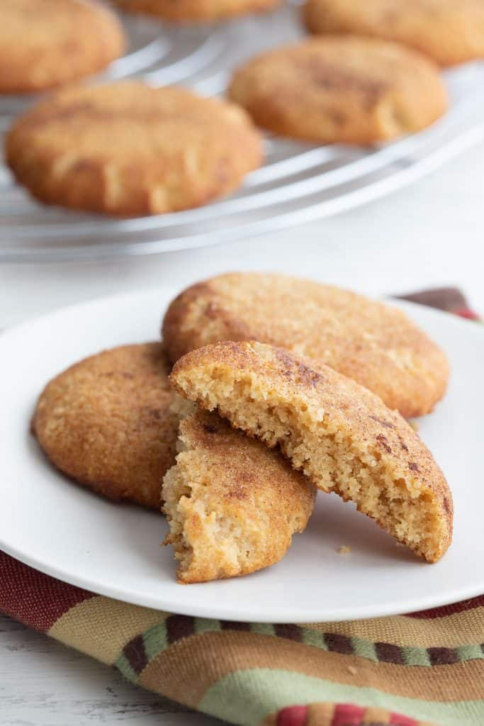 Keto snickerdoodles on a white plate with one broken open to show the inside.