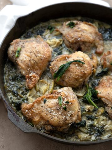 Six crispy chicken thighs with spinach and artichokes in a cast iron skillet.