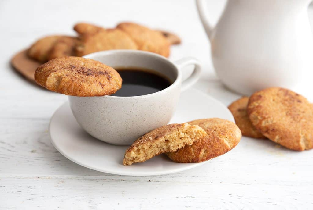 A cup of coffee on a white plate surrounded by keto snickerdoodles.