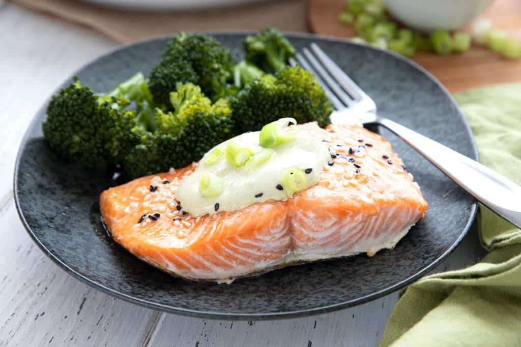 Perfectly roasted salmon on a black plate with broccoli and a fork.